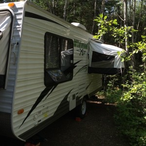 Side view of the camper nestled in the trees of Hecla Campground